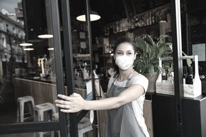 Worker opening the door at a cafe wearing a facemask.