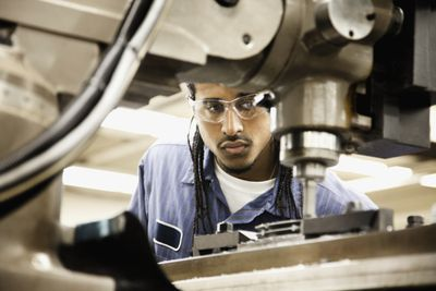 A man in goggles inspects machinery
