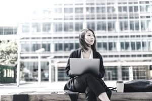 A young businesswoman reviews her investments on a laptop while sitting outdoors.