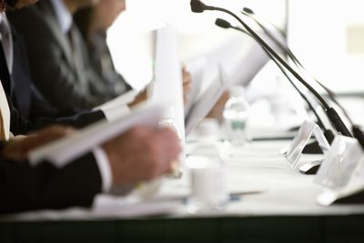 Managers sit at a conference table in front of microphones during a shareholder's meeting