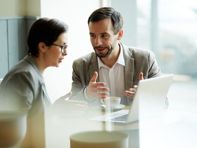 man and woman talking in front of computer