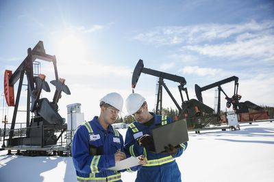 Engineers taking notes in oil rigs drilling for oil and representing crude oil futures.