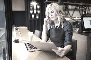 Cafe owner dealing with paperwork on the phone with laptop