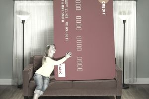 Woman sits on the sofa with oversized credit card
