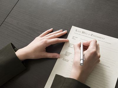 Closeup of a woman's hands signing a last will and testament