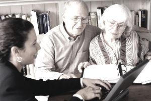An older couple meeting with a younger businesswoman at a laptop