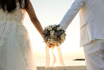 These newlyweds clutching a bouquet at the beach would be wise to set their tax filing status to married filing jointly