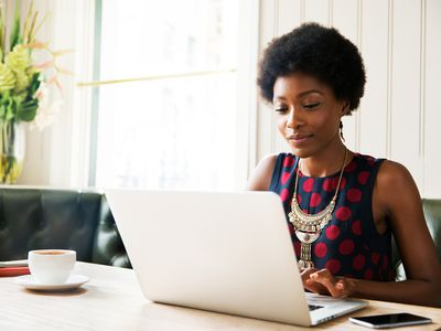 A woman reviews her investment gains on laptop at home