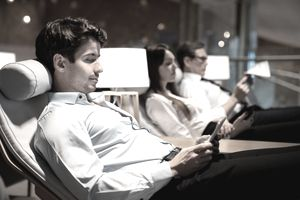 In a clean, dimly lit room, a man relaxes in a lounge chair and looks at his smartphone screen.