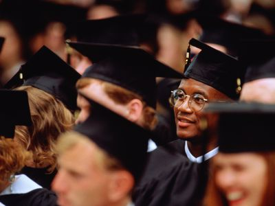 person wearing glasses standing in audience with graduation cap on