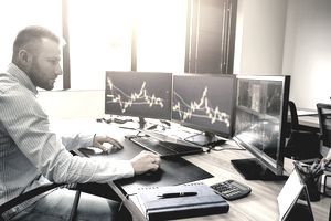 A man studying preferred stocks on several computers
