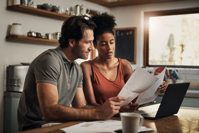 An affectionate young couple going through paperwork while doing their budget at home.