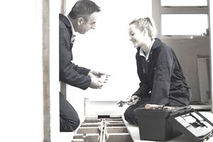 Male Tradesman Shows Young Female Apprentice a Tool at a Construction Site