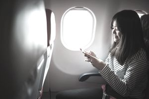 Young asian woman using smartphone on commercial flight