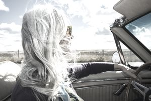 Platinum-haired woman driving a convertible on a sunny day