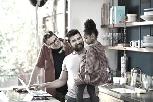 Gay couple online shopping with their daughter - stock photo