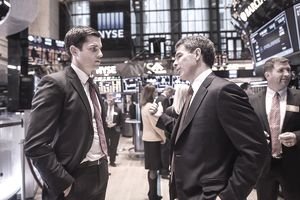 Men is suits talking on the floor of the NYSE