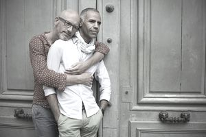 Two men stand in front of an old green door, one with his arms wrapped around the other from behind