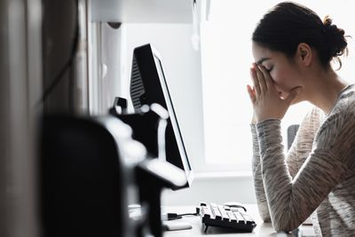 Distressed woman covering her face as she looks at computer