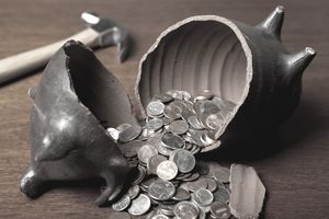 A broken piggy bank and a hammer as someone taps into an emergency fund.