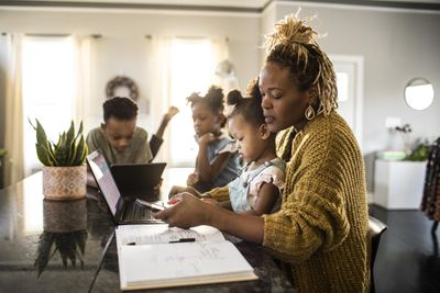 Mother working from home while holding toddler, family in background