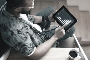 Young Man seated on stairs with a coffee cup reviewing a stock performance chart on a tablet device.