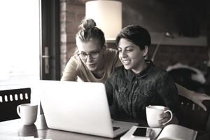 two women looking at computer in kitchen
