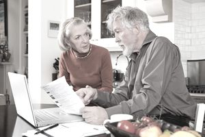 Senior couple looking concerned with bills and laptop