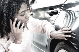 Woman on the phone next to scratched car
