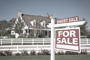 Short Sale, House for Sale sign in front of fenced two-story hone