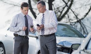 Two businessmen exchanging information about damaged cars