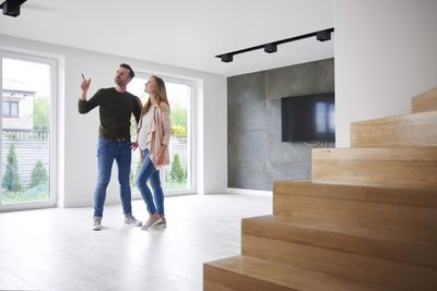 Young expectant couple examines modern condominium for sale