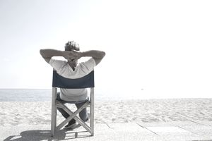 Man relaxing in chair at the beach, looking out a the ocean
