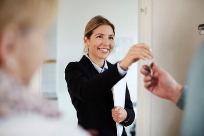 Confident smiling realtor giving house keys to couple