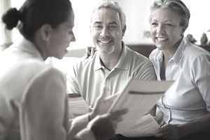 Mature couple listens to saleswoman going over paperwork