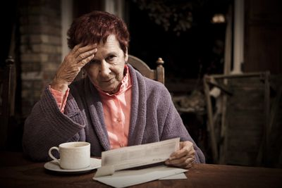 Older woman looking distressed as she reviews debt collections notice