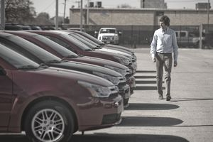 A man looking at certified pre-owned cars in a car lot