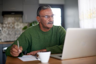 Person in green sweater writing down the best investment options