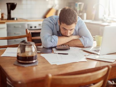 A concerned-looking man leaning on his crossed arms against a tabletop holding bills, a calculator, and a laptop