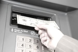 Woman withdrawing ten dollar note from cashpoint