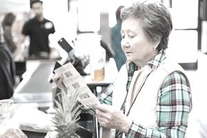 Prudent senior woman looking at her coupons before paying for her groceries.