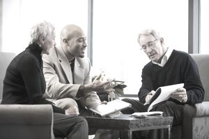 Financial Advisor Working With Two Older Clients on a Sofa and Chairs
