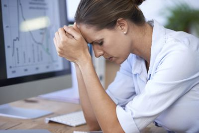 A frustrated woman leans her forehead on her hands while she sits at an office desk