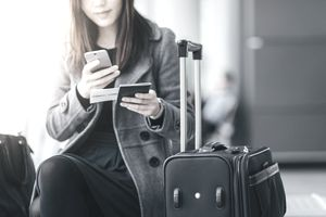 A woman looks at her phone and boarding pass while holding her passport and sitting in an airport next to her black rolling suitcase.