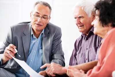 An elderly couple reviews some information on a sheet of paper while a man points out a detail with a ballpoint pen.