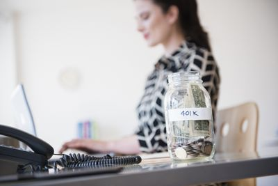 Woman working at a desk with a jar of cash labeled 401 K sitting on the desk..