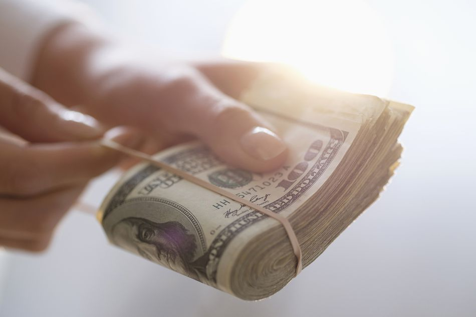 Woman holding rubber band around wad of cash