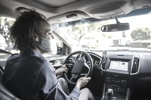 A rideshare driver with Uber wears a mask as she navigates through a neighborhood