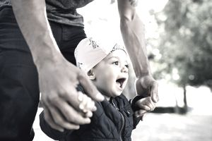 A baby smiles while holding the hands of an adult for support