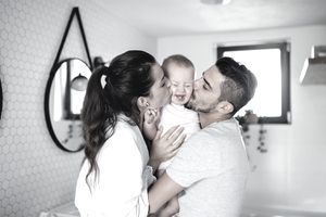 young couple with toddler girl in the morning indoors in bathroom at home, kissing.